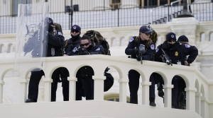 Police keep a watch on demonstrators who tried to break through a police barrier, Wednesday, Jan. 6, 2021