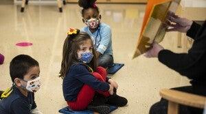 Pre-kindergarten students, in masks, listen as their teacher reads a story