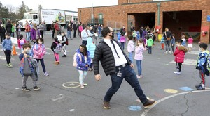 Aaron Condron-Lee leads his students to the classroom while they all wear masks