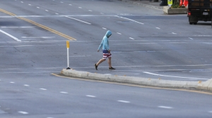 A person crosses an empty downtown street