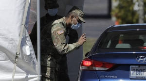 National Guard greets a visitor in a vehicle at a coronavirus testing site
