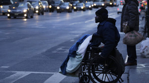 A man in a wheelchair has a blanket across his lap