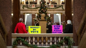 Public citizens hold up signs inside the Capitol calling for Republican lawmakers to respect their votes