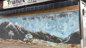 Hopeful messages and artistic creativity stand a stark contrast to broken, boarded-up windows