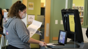 A poll worker inserting absentee ballots into a voting machine at the Lakeview Library on Madison's north side