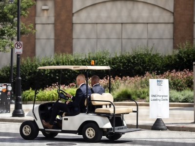 two bald men in suits ride in a golf cart