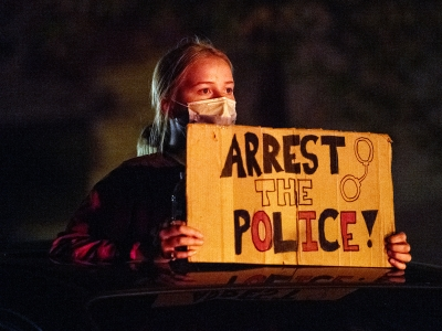 """A protester holds a sign that says """"arrest the police."""" She's is lit by a red tail light in an otherwise dark night."""