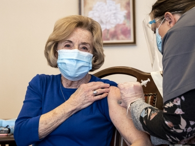 A woman in a blue shirt and blue face mask holds up a sleeve as she receives a shot