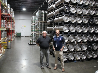 Steve and Mike Frank of Frank Beverage Group stand in front of kegs of Miller Lite and New Glarus Spotted Cow in their Middleton warehouse.