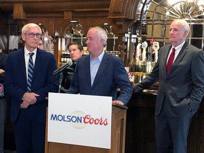 Tony Evers, Gavin Hattersley, and Tom Barrett at a podium