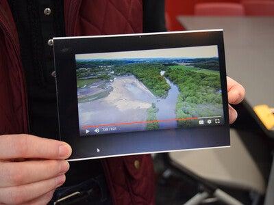 Vicky Grulkowski holds an image of farm flooding