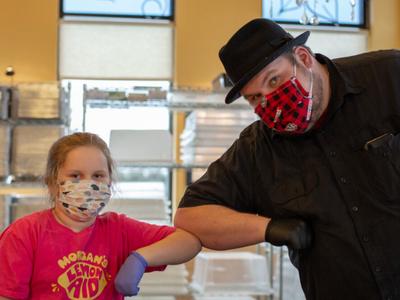 Morgan Marsh-McGlone bumps elbows withDave Heide, executive director of Little John's Kitchen in Fitchburg