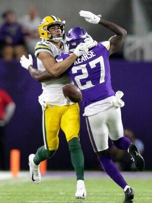 A Vikings defenders breaks up a Packers pass