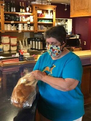 Barb Pratzel bags bread at Manna Cafe.