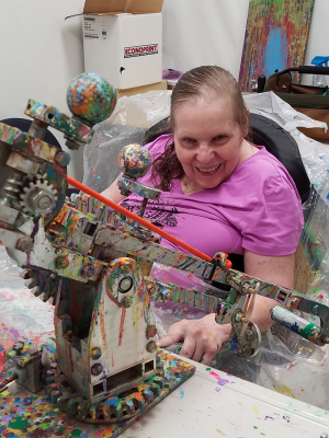Jeanne Grosse poses with an aluminum paint catapult that she uses to create artwork