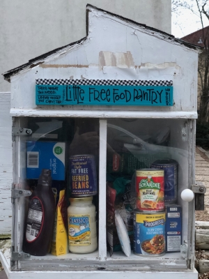 "A little house-shaped box with a sign that says ""Little Free Food Pantry"" is full of canned goods and other nonperishable foods."