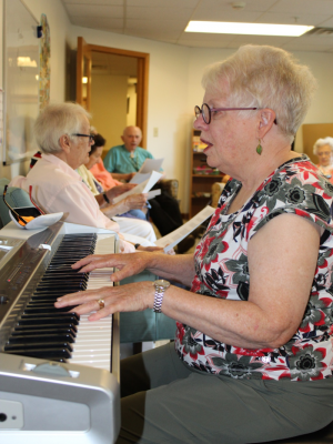 woman plays piano at Oakwood Village Prairie Ridge