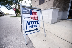 """A """"Vote Here"""" sign has an added sign about curbside voting"""