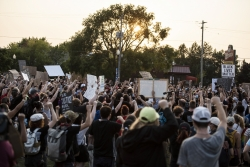 a sea of raised fists and signs take up a field in Kenosha