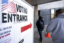 "A red arrow and a sign that says ""VOTING ENTRANCE"" guides voters to the polling location"