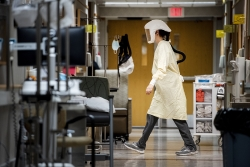 A woman in a yellow gown and protective hood walks through a hospital hallway
