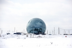 A large glass globe is surrounded by snow and a white cloudy sky.