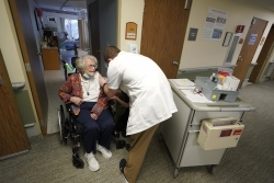 Jean Allen, 96, left, receives the first shot of the Pfizer vaccination for COVID-19