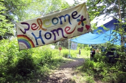 a sign welcomes people to the gathering of the Rainbow Family of Living Light