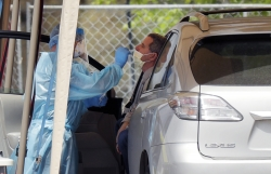 A medical worker tests a person for the coronavirus at a drive-through facility