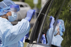 A medical assistant reaches in to take a nasal swab from a driver at a drive-up coronavirus testing site