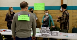Poll workers at Mendota Elementary School on Madison's north side discuss absentee ballot counting