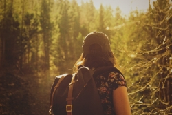 A girl wearing a backpack faces away from the camera on a wooded trail.