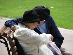 An elderly couple sits together on a park bench