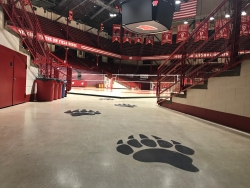Big, black badger footprints painted on the floor lead to a volleyball court. The arena is all Wisconsin red and white.