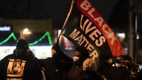 a black lives matter flag is held up by a protester in a face mask