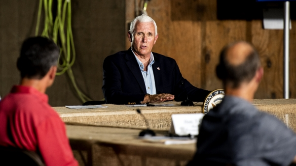 Vice President Mike Pence looks toward people at a round table