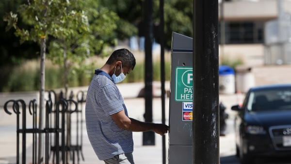 A man pays at a parking meter machine while wearing a mask