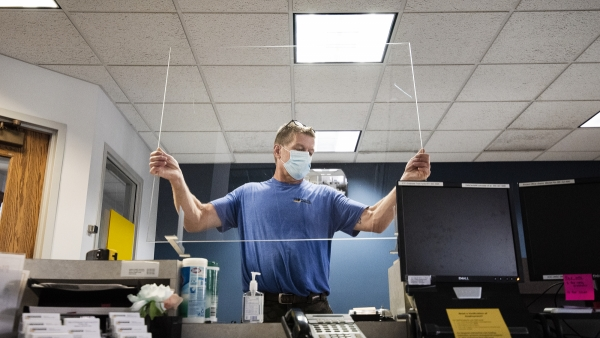 a man in a mask lifts a piece of plexiglass above a desk