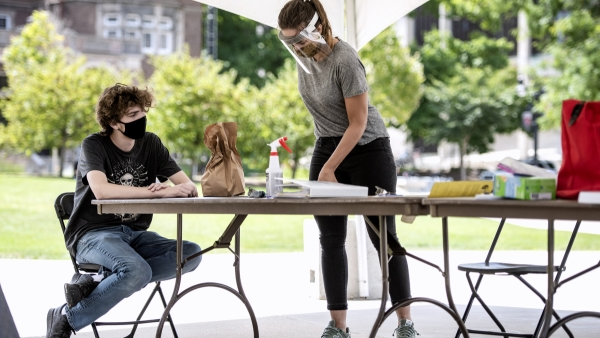 a man in a mask sits outdoors at a table as a poll worker in a face shield gives instructions