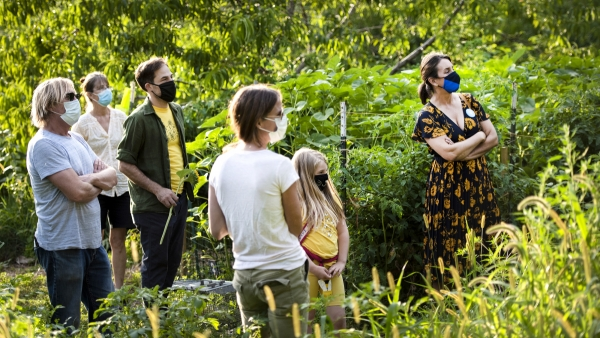 a group of people in face masks are surrounded by greenery as they listen to a speaker