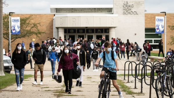 a student in a mask rides a bike as a sea of high school students, some wearing masks, exit the school
