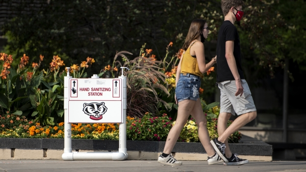 two people walk by some hand sanitizer on a small stand displayed with the image of Bucky badger
