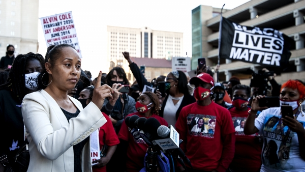 a woman in a suit jacket holds up her finger as she speaks to protesters gathered closely together