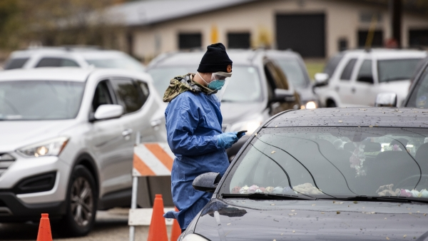 a man in a blue gown and face covering uses a phone as he approaches a vehicle in line for the test