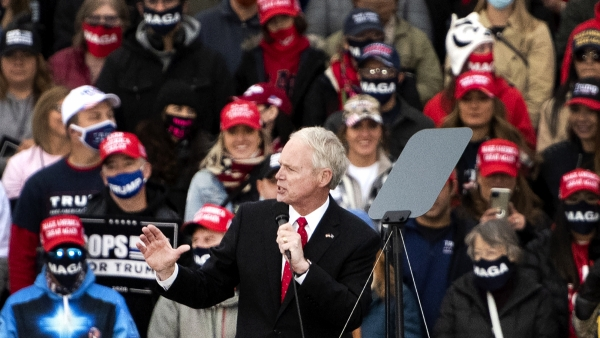 Trump supporters in MAGA hats can be seen behind Sen. Ron Johnson as he speaks into a microphone