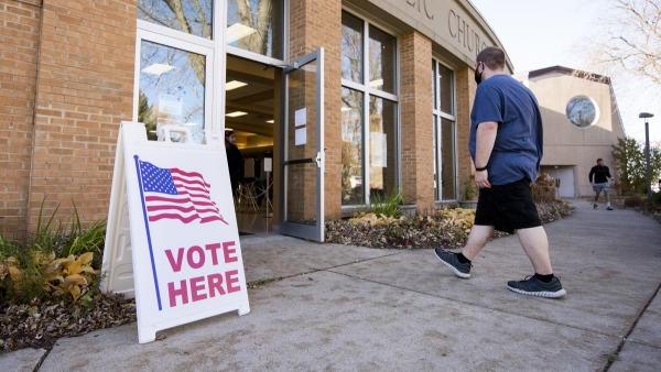 "a voter walks into a polling location. a sign says ""vote here."""