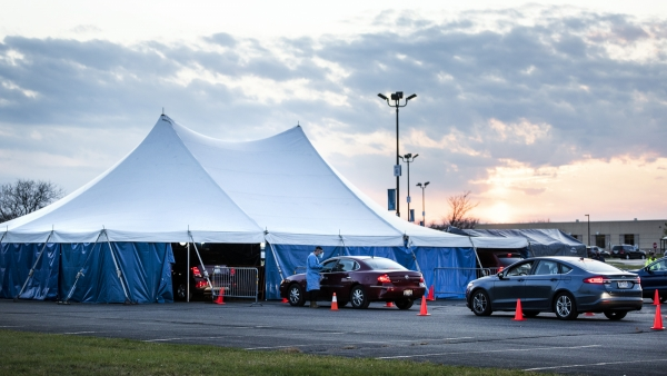 A tent is set up for vehicles to drive through and receive COVID-19 testing