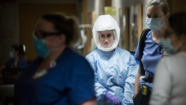A woman in a blue gown, purple gloves, and a large white hood with a clear plastic window pulls up a glove as she walks through a hallway with other healthcare workers