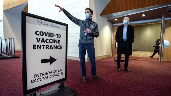 """Two men in face masks stand by a sign that says """"COVID-19 Vaccine Entrance"""""""