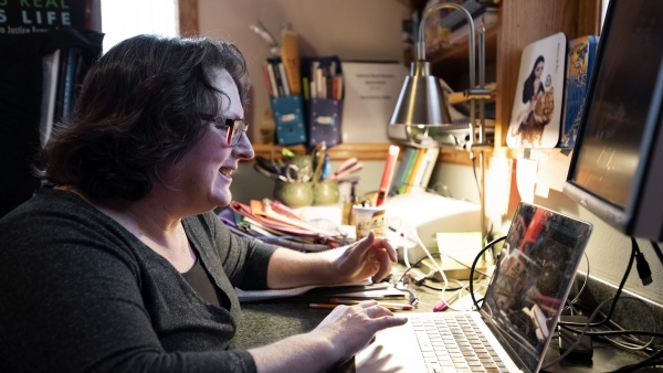 a woman sits in front of a laptop as she speaks to students. A desk lamp and various pictures surround her at her desk.